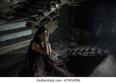 photo of a jester woman holding hands near face while sit inside a dark stone staircase deep inside the basement of a vintage haunted castle. Halloween concept