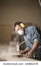 Photo of joiner labouring in mask and glasses for safety