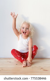 Photo of joyful blonde small kid sits on wooden floor, dressed casually, raises hand, isolated over white background. Cute lovely girl with cheerful expression. Children and emotions concept.