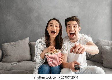 Photo of joyful couple smiling and sitting on sofa at home with pointing finger at you while watching tv and eating pop corn
