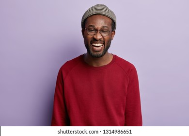 Photo of joyful dark skinned man with stubble, laughs happily, wears hat and red jumper, expresses positive emotions, isolated over purple background. African American young male grins at camera