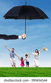 Photo of joyful family running on the meadow while holding hands under umbrella. Life and family insurance