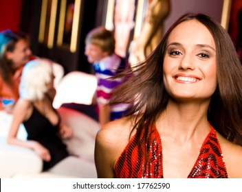 Photo of joyful girl laughing in a night club and looking at camera