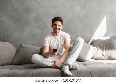 Photo of joyful man 30s in casual clothing sitting on sofa in living room and looking on camera with remote control in hand