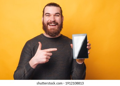 Photo of joyful man with beard pointing at tablet over yellow background.