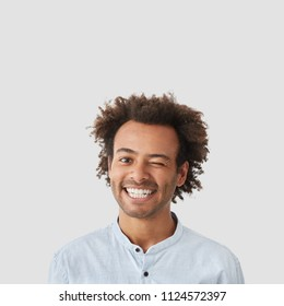 Photo of joyful mixed race young man blinks with eye, has broad shining smile, white teeth, happy to meet with beautiful woman, isolated over white studio background. Positive emotions concept