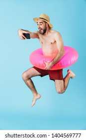Photo of joyful shirtless tourist man wearing rubber ring smiling and holding cellphone isolated over blue background
