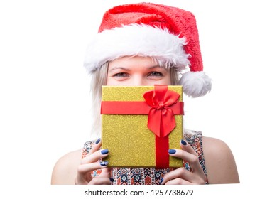 Photo of joyful woman in Santa's cap with gift on face
