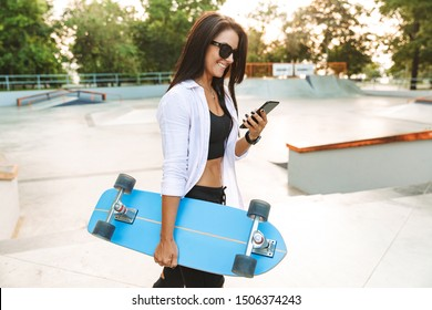 Photo of joyful young woman in streetwear smiling and holding cellphone while carrying skateboard in park