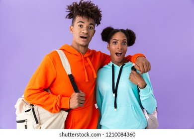 Photo of joyous african american brother and sister wearing backpacks hugging together isolated over violet background