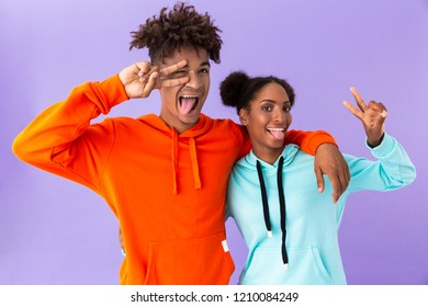 Photo of joyous african american couple standing together and showing peace sign isolated over violet background