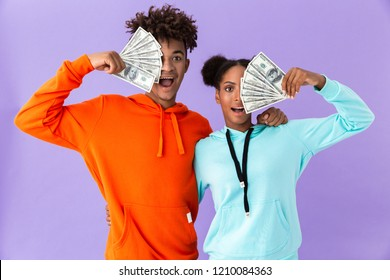 Photo of joyous african american couple in colorful clothes holding fans of dollars money isolated over violet background