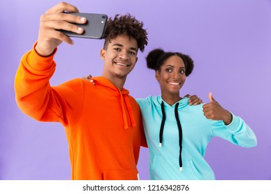 Photo of joyous african american couple wearing colorful sweatshirts taking selfie on smartphone isolated over violet background