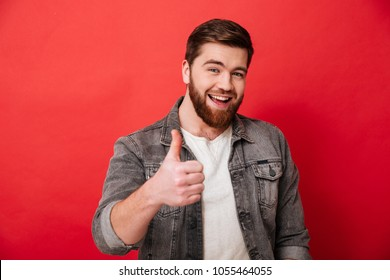 Photo of joyous bearded guy 30s in jeans jacket smiling and showing thumb up on camera isolated over red background
