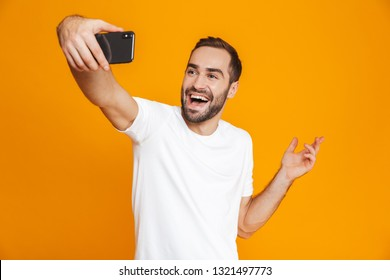 Photo of joyous guy 30s in casual wear laughing and taking selfie on cell phone isolated over yellow background