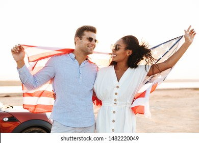 Photo of joyous multiethnic couple man and woman smiling and holding american flag while standing by car outdoors