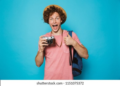 Photo of joyous traveler boy 18-20 with curly hair wearing backpack and straw hat photographing on retro camera isolated over blue background