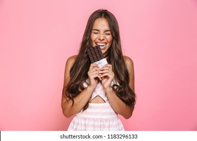 Photo of joyous woman 20s wearing dress smiling and eating chocolate bar isolated over pink background