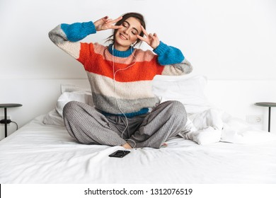Photo of joyous woman 20s wearing earphones lying in bed at home and using cell phone