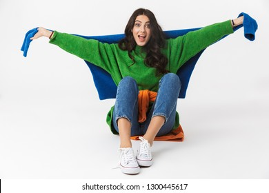 Photo of joyous woman 30s with dark hair in colorful clothes sitting on the floor isolated over white background
