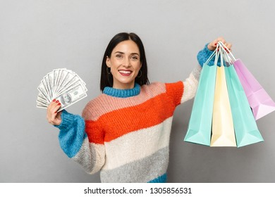 Photo of joyous woman 30s holding bunch of money and shopping bags isolated over gray background