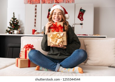 Photo of joyous woman sitting on sofa in living room with gift boxes while celebrating New Year