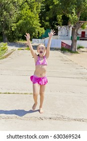 Photo of jumping girl on the riverbank in pink swimsuit