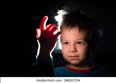 photo of a kid in the dark looking with great curiosity at his hand in a ray of light
