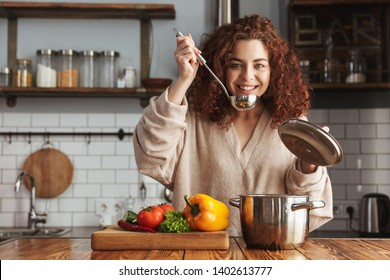 Photo of kind caucasian woman holding cooking ladle spoon while eating soup with fresh vegetables in kitchen at home