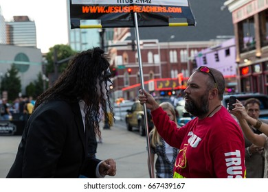 Photo of KISS fan arguing with man holding sign that had a Bible verse on it outside of the July 16, 2014 KISS concert in Nashville, TN outside the Bridgestone Arena on Broadway.