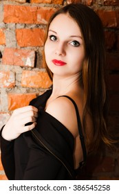 photo of Lady in black dress over a brick wall