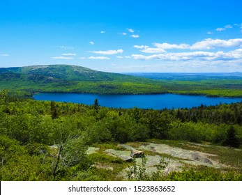 Photo of landscape with lake, mountain, and trees; view from Cadillac Mountain in Acadia National Park in Maine, USA