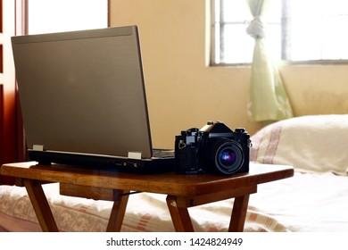 Photo of a laptop computer and a manual, 35mm film camera on a table inside a bedroom