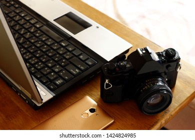 Photo of a laptop computer, smart phone and a manual, 35mm film camera on a table inside a bedroom