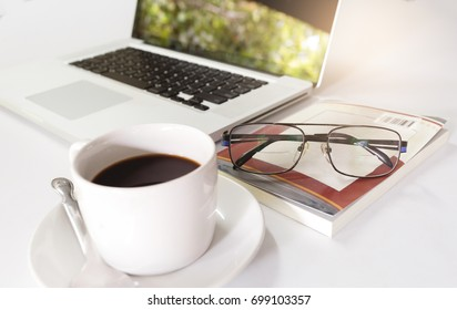photo of laptop glasses book and coffee on white table