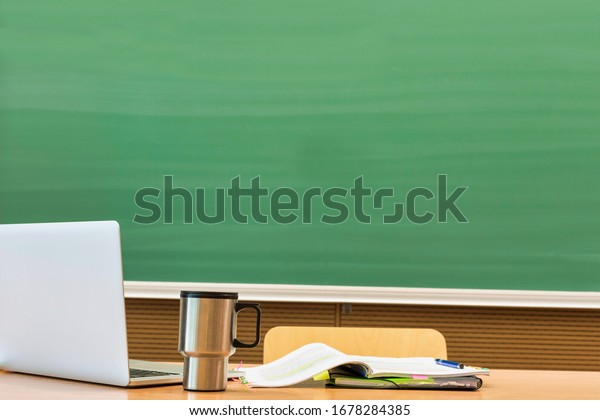 Photo of laptop on professor desk with tumbler and book against black board in classroom there are no classes taking place due to the corona covid-19 infection