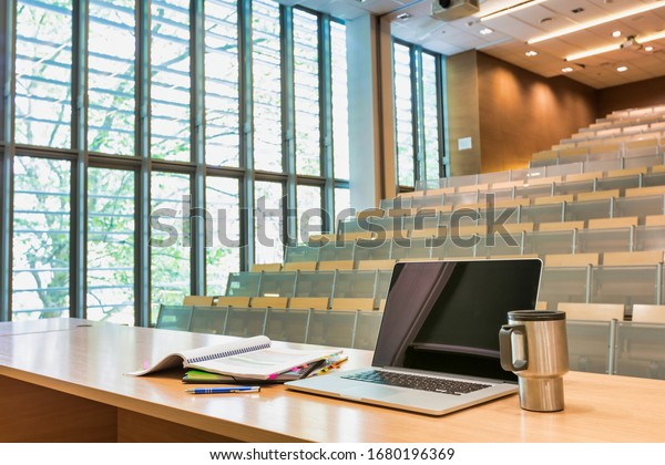 Photo of laptop on professor desk with lesson plan and tumbler in empty classroom due to coronavirus