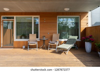 Photo of large empty space on terrace with wooden floor, wall and furniture chair and table in modern house