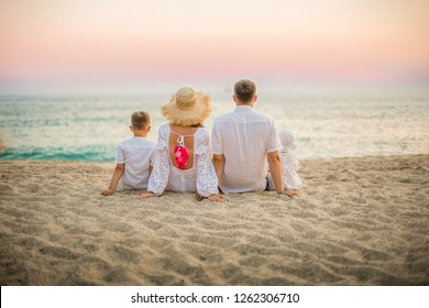 Photo of a large family in white closes on the beach. The family sits on the beach, ocean, sand image. Happy family on vacation, posing from the back without faces picture.