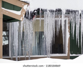 A photo of a lot of large icicles hanging down from a cabin roof overhang.