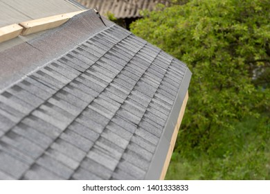 Photo of layer of installing asphalt or bitumen shingle on top of the new roof under construction residential house or building against green nature background