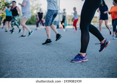 Photo of legs in sportswear and shoes dancing zumba during the class outside on the street