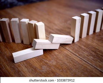 Photo of light beige wooden bricks arranged in a row like a domino row, with some of the bricks lying on the floor. Construction concept. Failure concept.