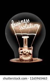 Photo of light bulb with shining fiber in BUSINESS SOLUTION shape isolated on black background