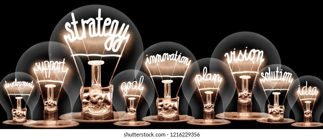 Photo of light bulbs group with shining fibers in a shape of STRATEGY concept related words isolated on black background