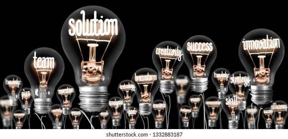 Photo of light bulbs group with shining fibers in a shape of SOLUTION and INNOVATION concept related words isolated on black background