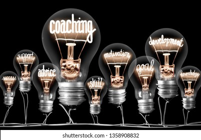 Photo of light bulbs group with shining fibers in a shape of Coaching concept related words isolated on black background
