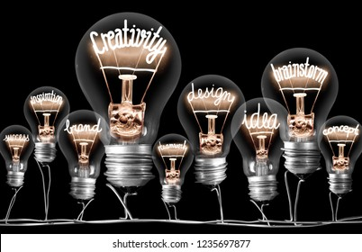 Photo of light bulbs on wires with shining fibers in a shape of CREATIVITY concept related words isolated on black background
