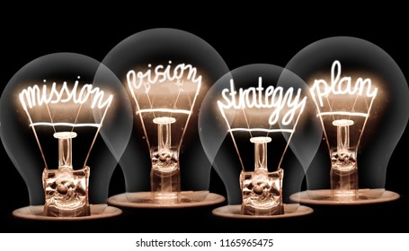 Photo of light bulbs with shining fibers in MISSION, VISION, STRATEGY and PLAN shape on black background