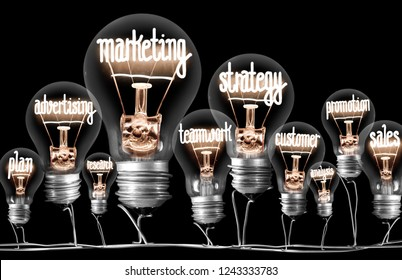 Photo of light bulbs with shining fibers in shapes of MARKETING concept related words isolated on black background